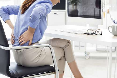 woman in chair with back pain