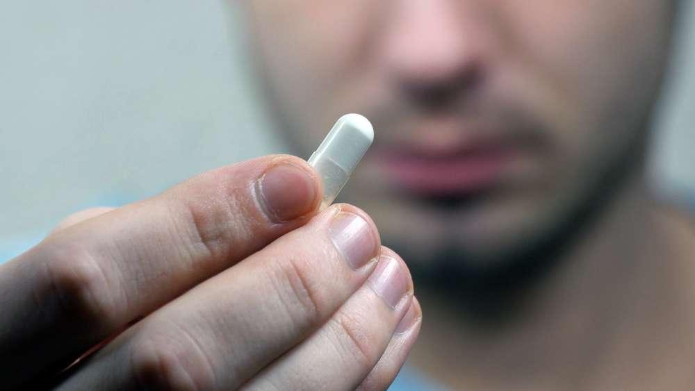 man holding pill
