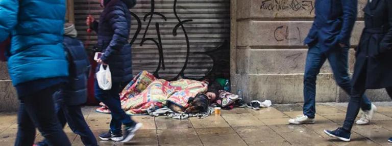 person lying on sidewalk in a city