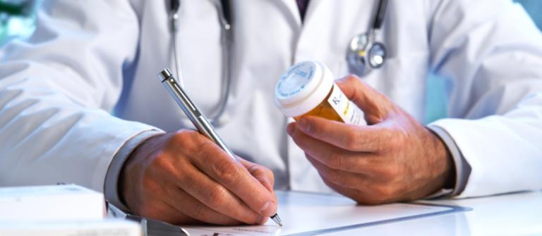 Doctor writing prescription for pills