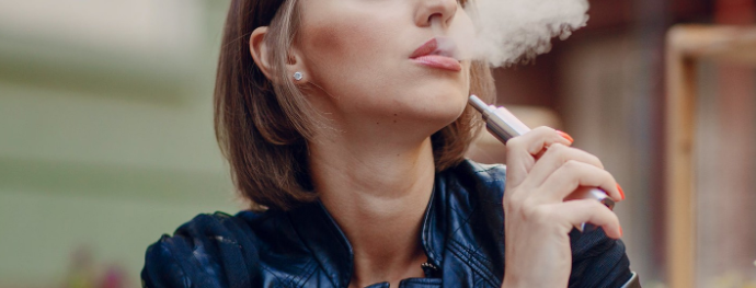 Woman using Iqos vaping device