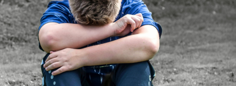 child sitting alone head bowed